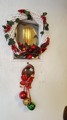 front door decorations: white wreath with berries and 3 sleigh bells