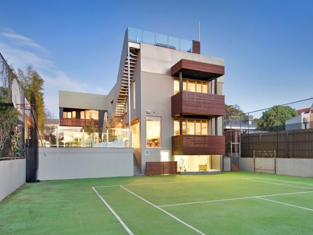 Photo of amazing modern home as seen from the tennis court in the backyard
