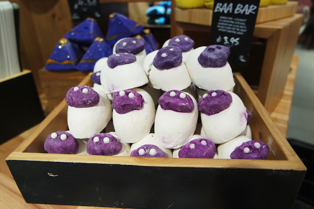 a stack of white bath bombs with purple faces and white eyes, made to look like sheep