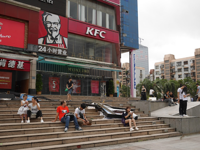 people sitting next to typhoon debris in front of a KFC in Zhuhai