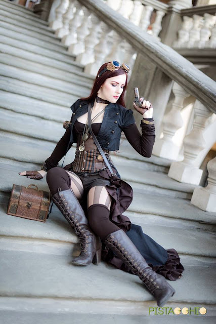 Woman dressed a Steampunk hunter (or huntress) in striped stockings, boots, goggles, corset, shorts and skirt.