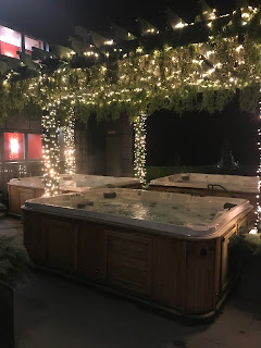 outisde hot tub with fairy lights and green hanging plants
