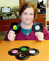 Woman holding up two small vinyl records