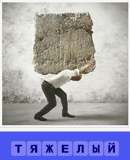 мужчина согнувшись на спине несет тяжелый камень