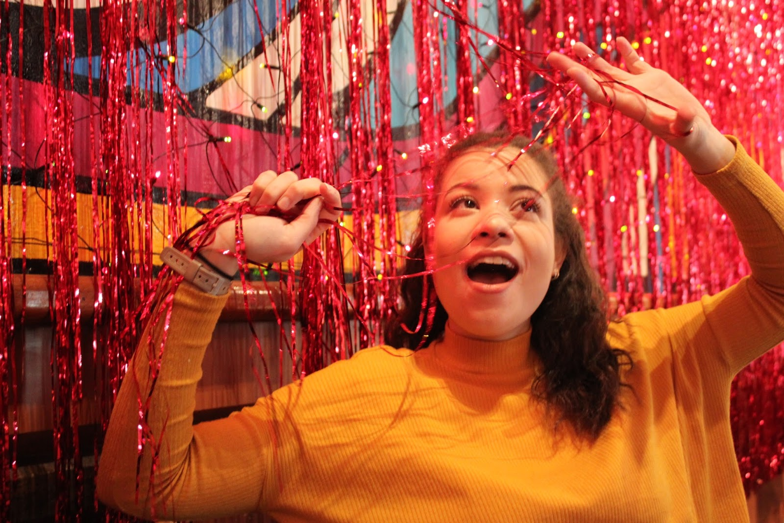 Eboni being silly with the Cafe Schuim wall tinsel in Amsterdam.