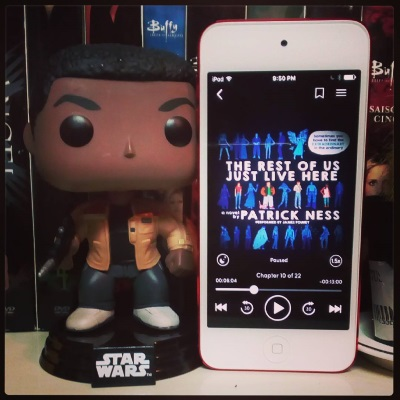 A large-headed Funko Pop bobblehead of Finn from Star Wars stands next to a white iPod with the cover of The Rest Of Us Just Live Here on its screen. The cover is black, covered in three rows on people in shades of blue. One white girl, two white boys, and one black girl are in full colour.