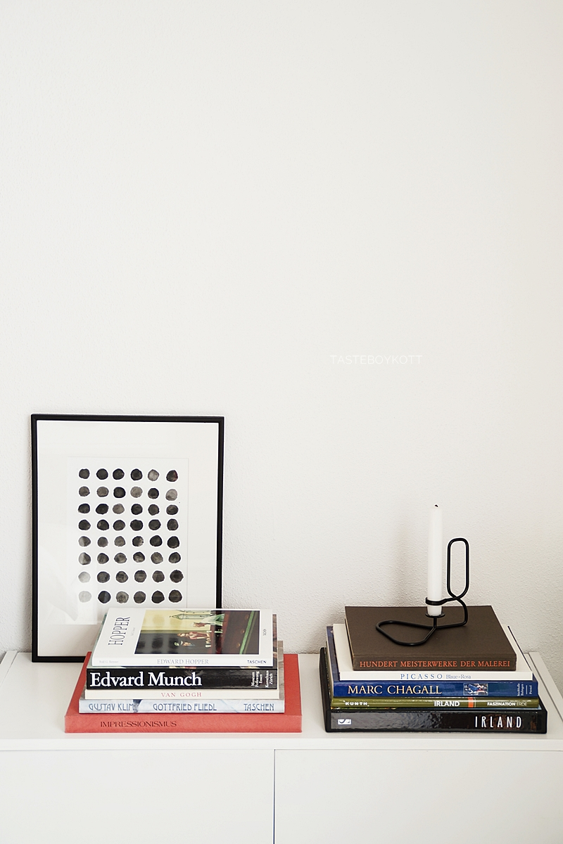 Modern minimalist white Scandinavian decorated interior design sideboard with big stacks of coffee table books