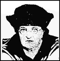 A poor quality picture of a white woman of late middle age, with sharp features, wearing round spectacles and a sailor-style blouse and hat
