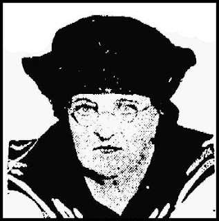 A newspaper image of a middle-aged white woman with stern features and wire-rimmed glasses, wearing a dark sailor-style hat and blouse with sailor-style collar