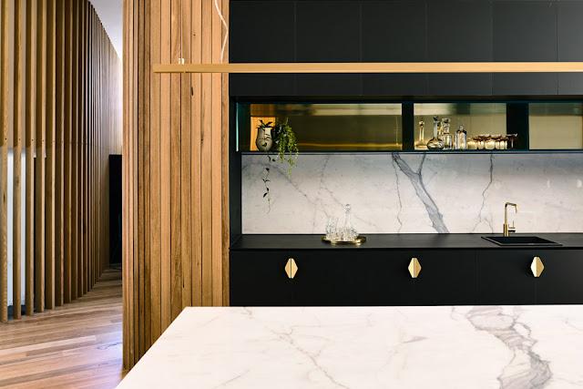 Maison contemporaine dans la verdure cuisine bois marbre et laiton