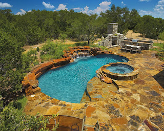 wonderful backyard design with broken stone flooring around  pool with hot tub near open kitchen with slate fireplace