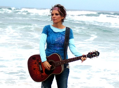Foto de Soraya con su guitarra en la playa