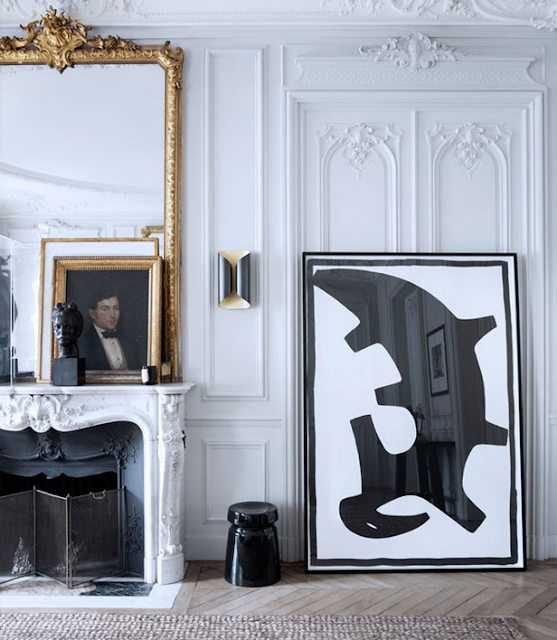 Gilles & Boissier design with an elavorate white stone fireplace, black art and sconces via belle vivir blog
