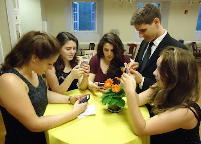 five young people sitting around a table texting on their cell phones