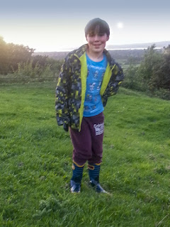Boy wearing Bogs Wellies, standing on a hill.