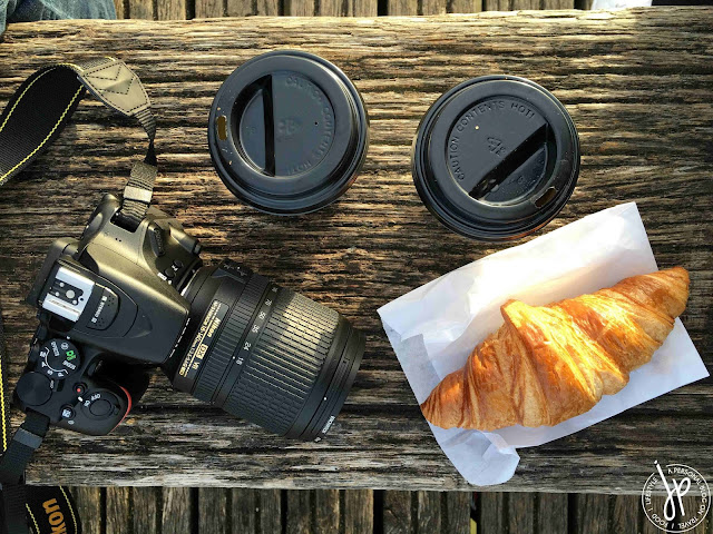 digital camera, two coffee cups, croissant on the bench