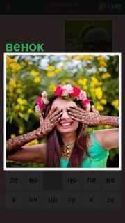 девушка закрыла глаза и на голове у неё венок из цветов