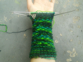 An image of textured mittens.  They're half-completed on dpns, and being worn on the left hand.  The yarn is varigated green/black/blue, and there's a locking stitch marker with a silver celtic knot visible.