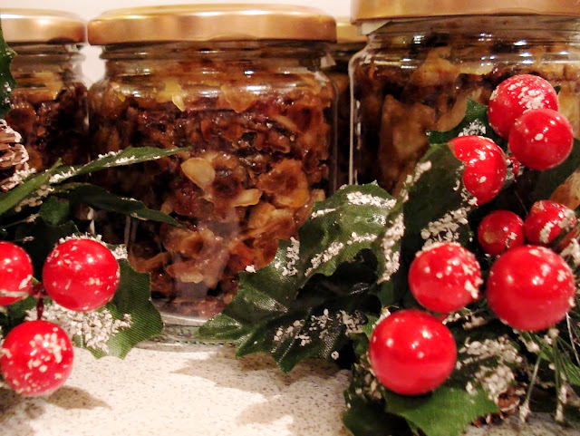 Sweet mincemeat in jars with holly and red berry decoration