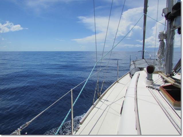 A vintage sailboat glides through calm cobalt seas.