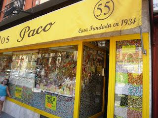 Fachada de la tienda, de color amarillo y con grandes ventanales totalmente llenos de caramelos, piruletas y otras golosinas.