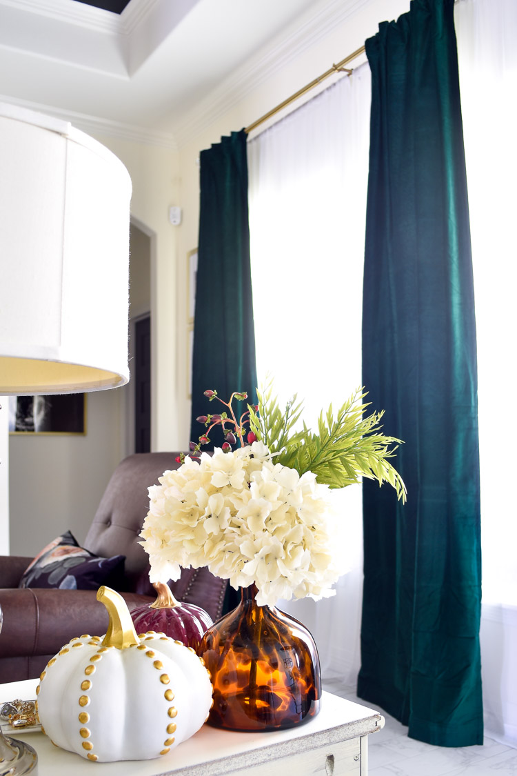 An eclectic living room featuring dark green velvet curtains, white walls and chinoiserie inspired home decorations.