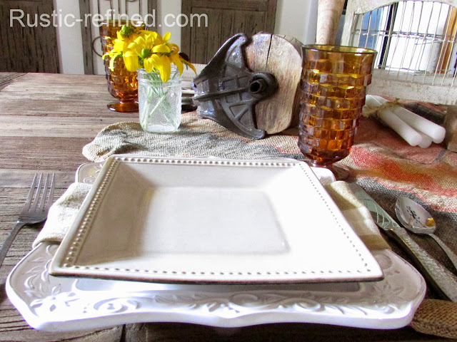 Simple rustic tablescape using wood tone colors white dishes and amber colored glasses.