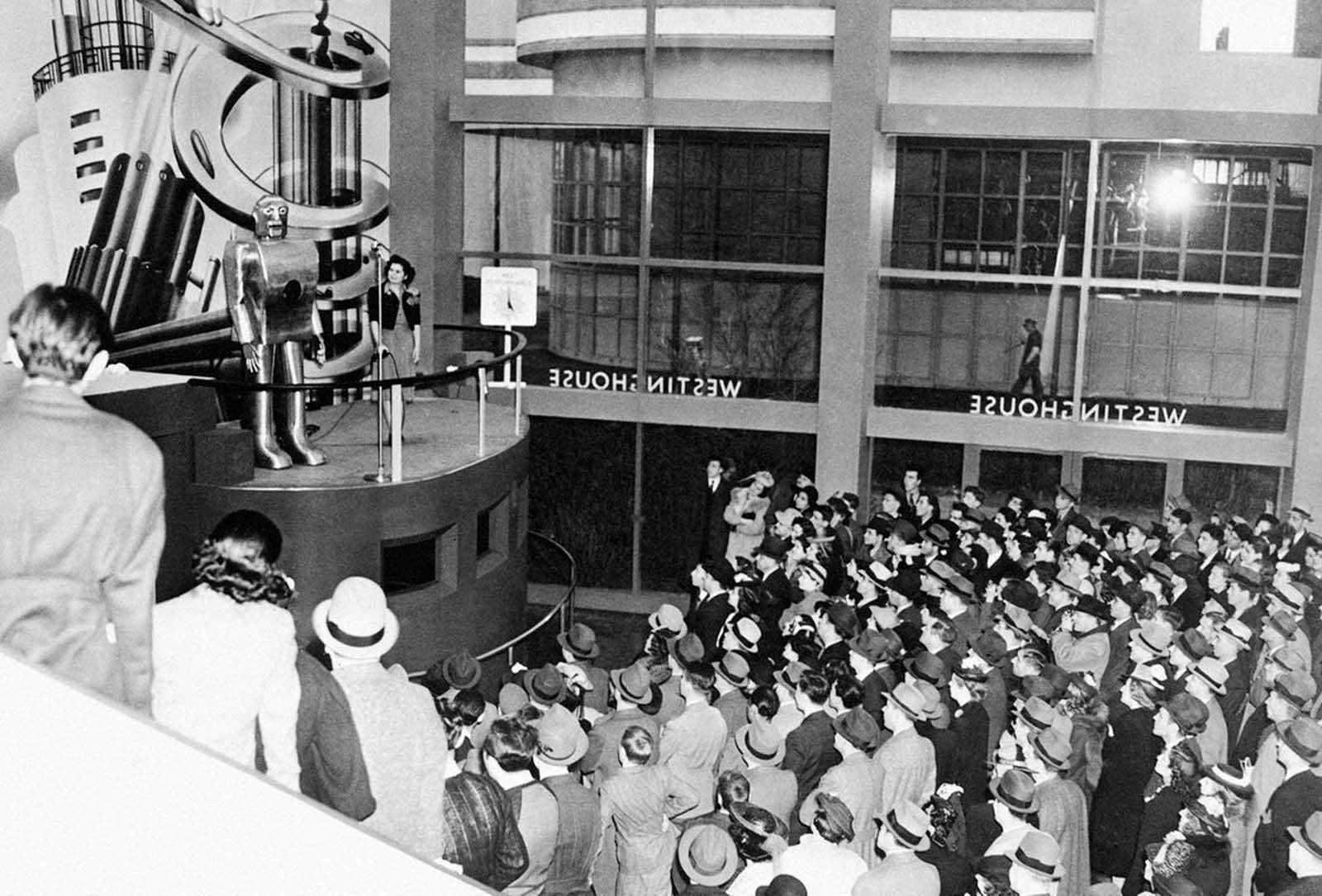 Jamming every inch of space in the huge Hall of Electrical Living at the Westinghouse Building at the World's Fair, crowds stand 6 deep on the sidewalk outside the glass-enclosed structure to watch Elektro, the Westinghouse Moto-Man, perform his 26 mechanical tricks, including, walking, talking, smoking a cigarette and counting, on May 8, 1939.