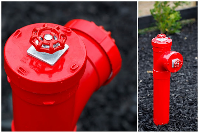 Homemade shiny red fake fire hydrant dog pee post in the garden