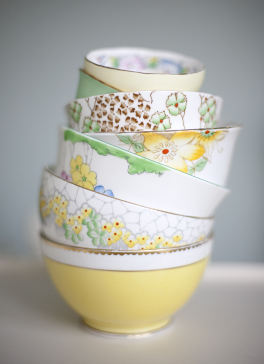 a stack of floral yellow and green vintage sugar bowls