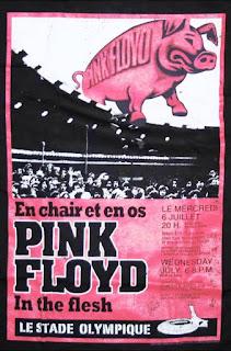 Cartel de Pink Floyd-In The Flesh. Muestra un escenario, público, texto negro sobre fondo rosa y arriba un gran cerdo en el que podemos leer: Pink Floyd