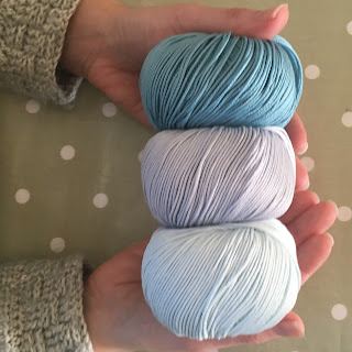 My hands holding three balls of yarn