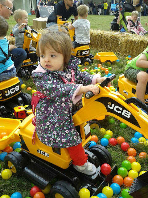 Eldest on a mini JCB Digger among balls suitable for a ball pool