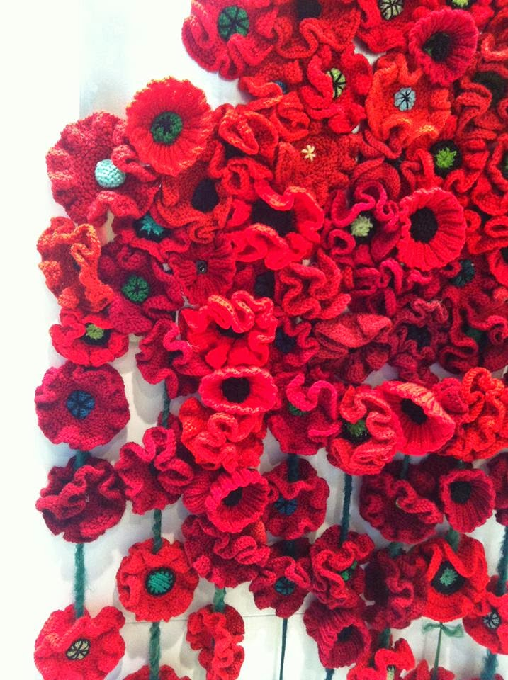 Lots of knitted and crocheted poppies displayed together. There are many different styles of handcrafted poppies mixed together.  Photo used with permission from Madison Prime.