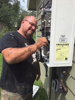 A plumber stands next to a 3 foot by 4 foot white metal box mounted on the outside wall of a house. He uses a small tool to fix the guts of the machine.