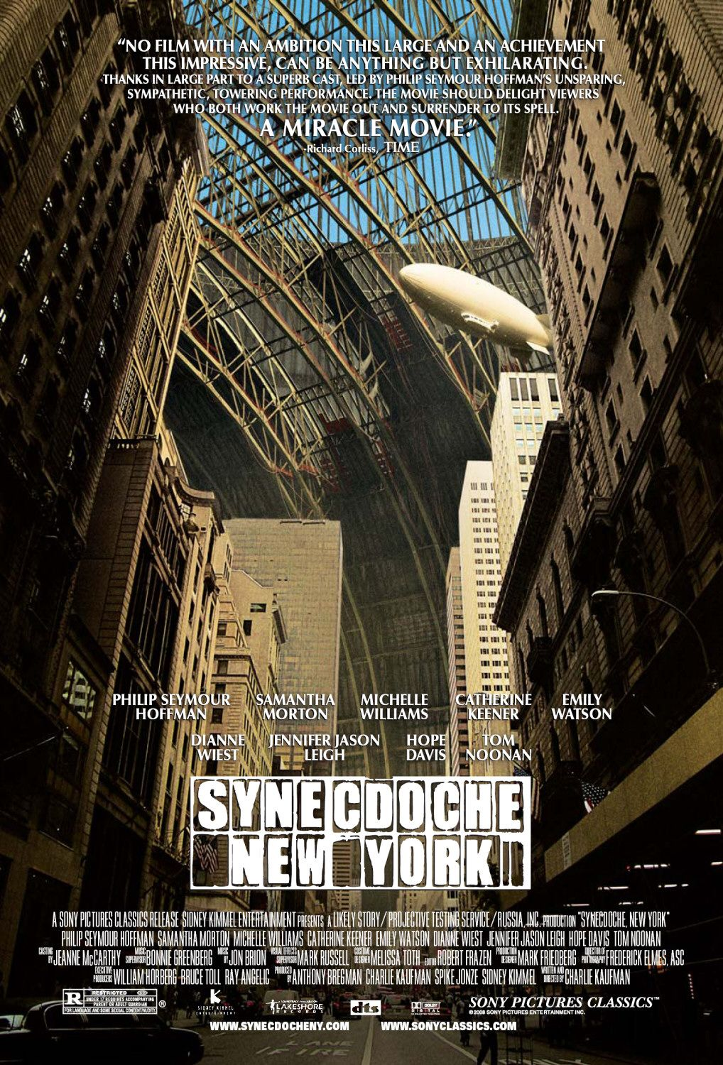 The theatrical release poster for Synecdoche, New York. It is a photograph of a city street, taken from the middle of the street. Tall buildings dominate the foreground of the image. A zeppelin is prominent in the background with curved metal beams enveloping the entire scene and blocking out the skyline.