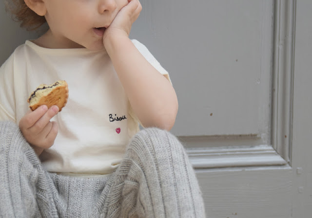 child eating pastry with grey blue vintage door