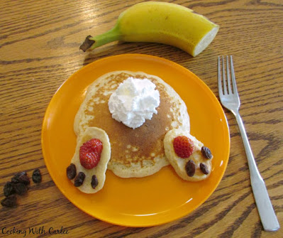 bunny butt pancake on orange plate with banana and additional raisins