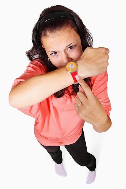 Frau zeigt auf eine Uhr