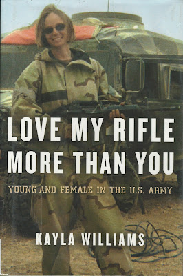 Shows young woman in combat uniform with large automatic rifle in front of a military vehicle