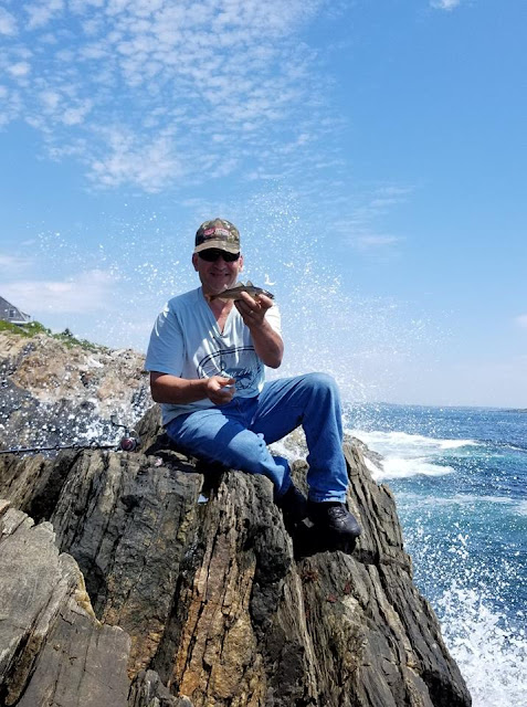 a man in a ball cap, tee shirt, and jeans sitting on a large rock near the ocean, holding a fish