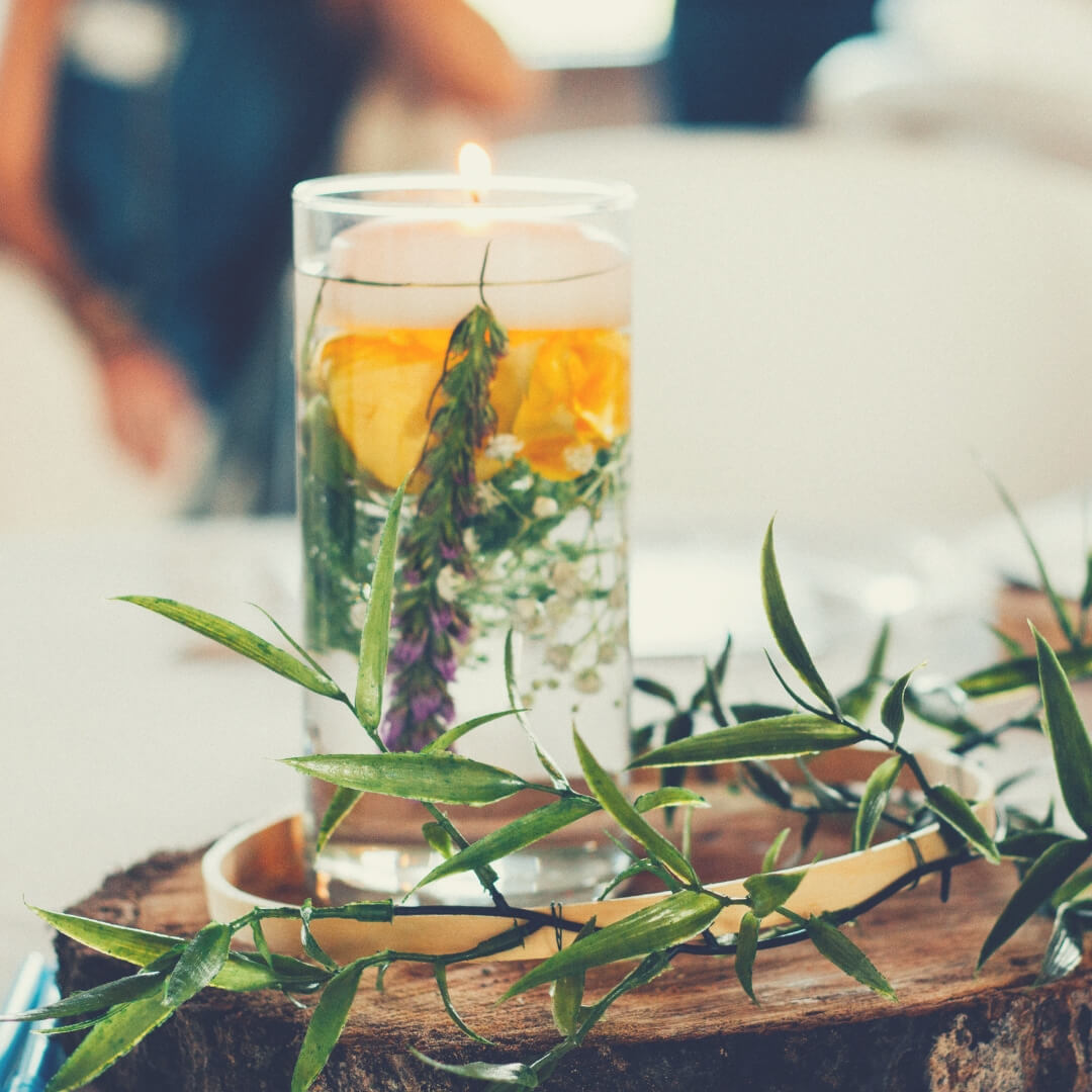 Post Comment Love 5th - 7th October | A glass filled with water and flowers, behind it a woman sits waiting.
