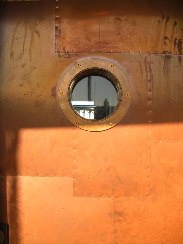 Close up photo of small round window on entrance doors