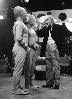 William Hartnell as Dr Who, peers through his monocle at two extra-terrestrials during filming of the popular science fiction series, 'Dr Who' at the BBC's Shepherds Bush Studios in London.   (Photo by Harry Todd/Getty Images)