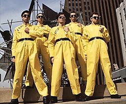 Fotografía de DEVO. Los 5 integrantes con trajes amarillos y gafas negras