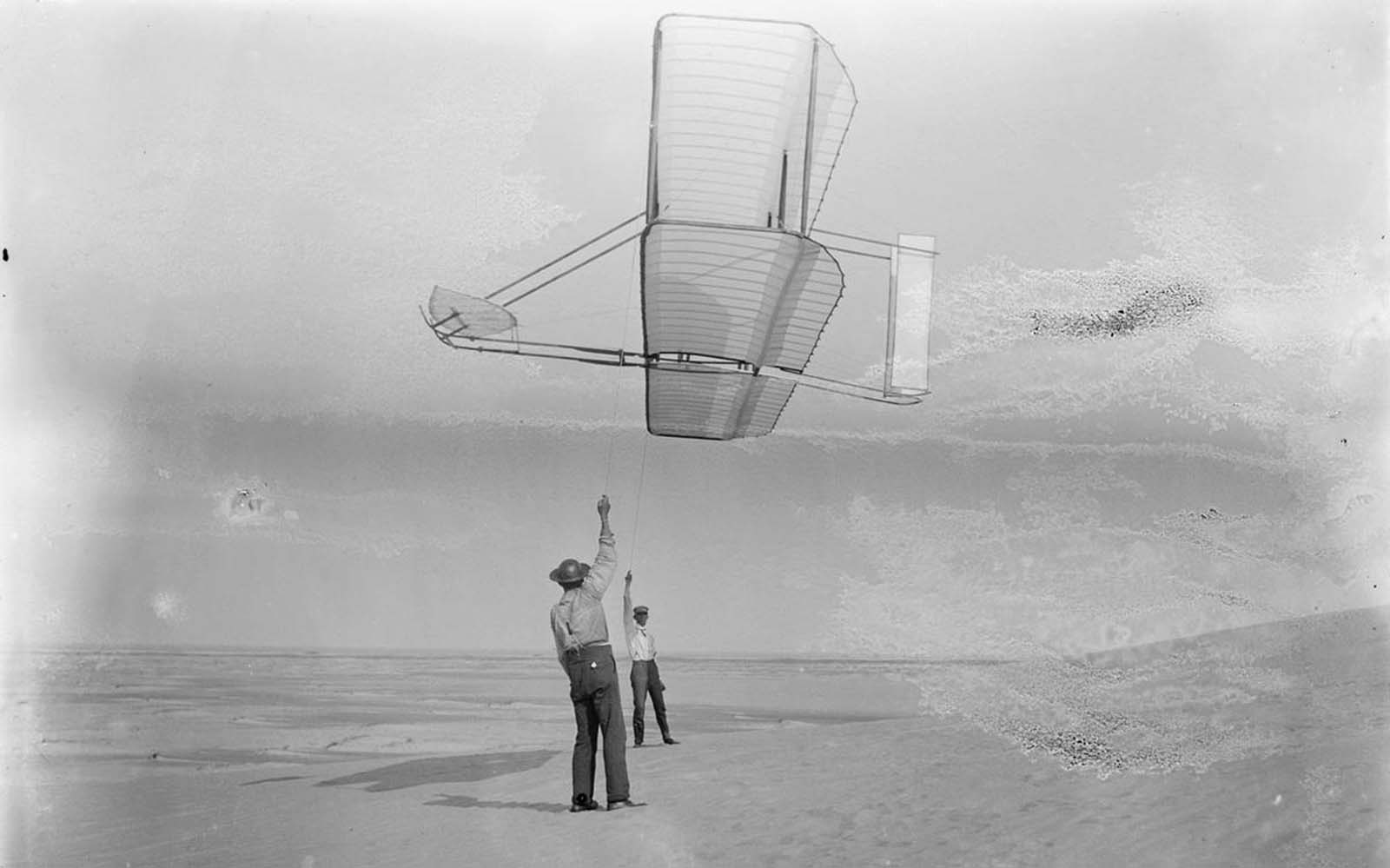 Side view of Dan Tate, left, and Wilbur Wright, right, flying the 1902 glider as a kite, on September 19, 1902.