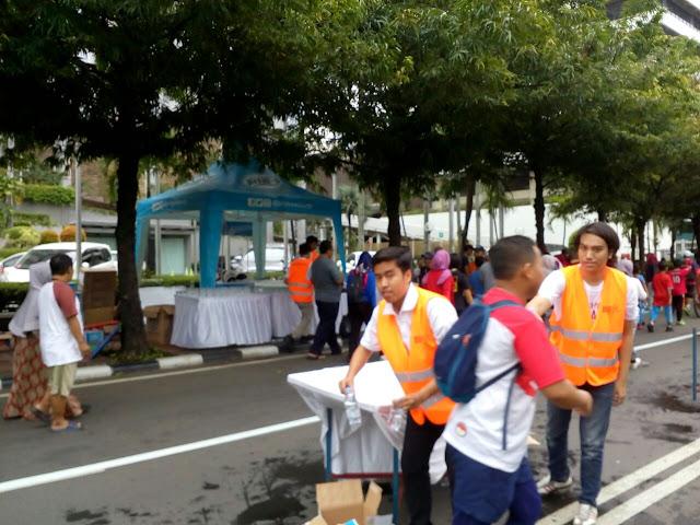 Panitia memberikan air kepada peserta lari