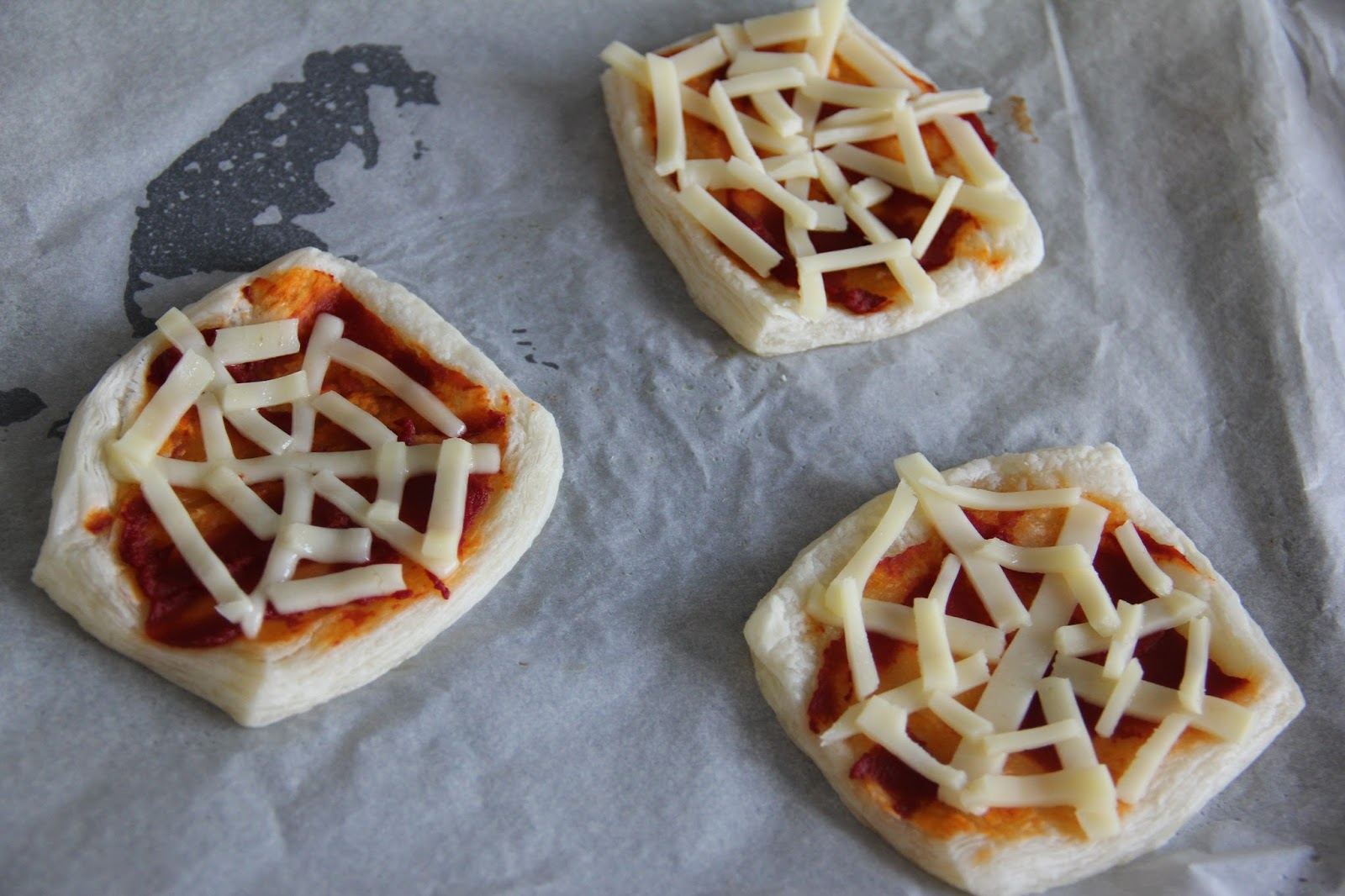 Mozzarella spider web pizza, ready to go back in.