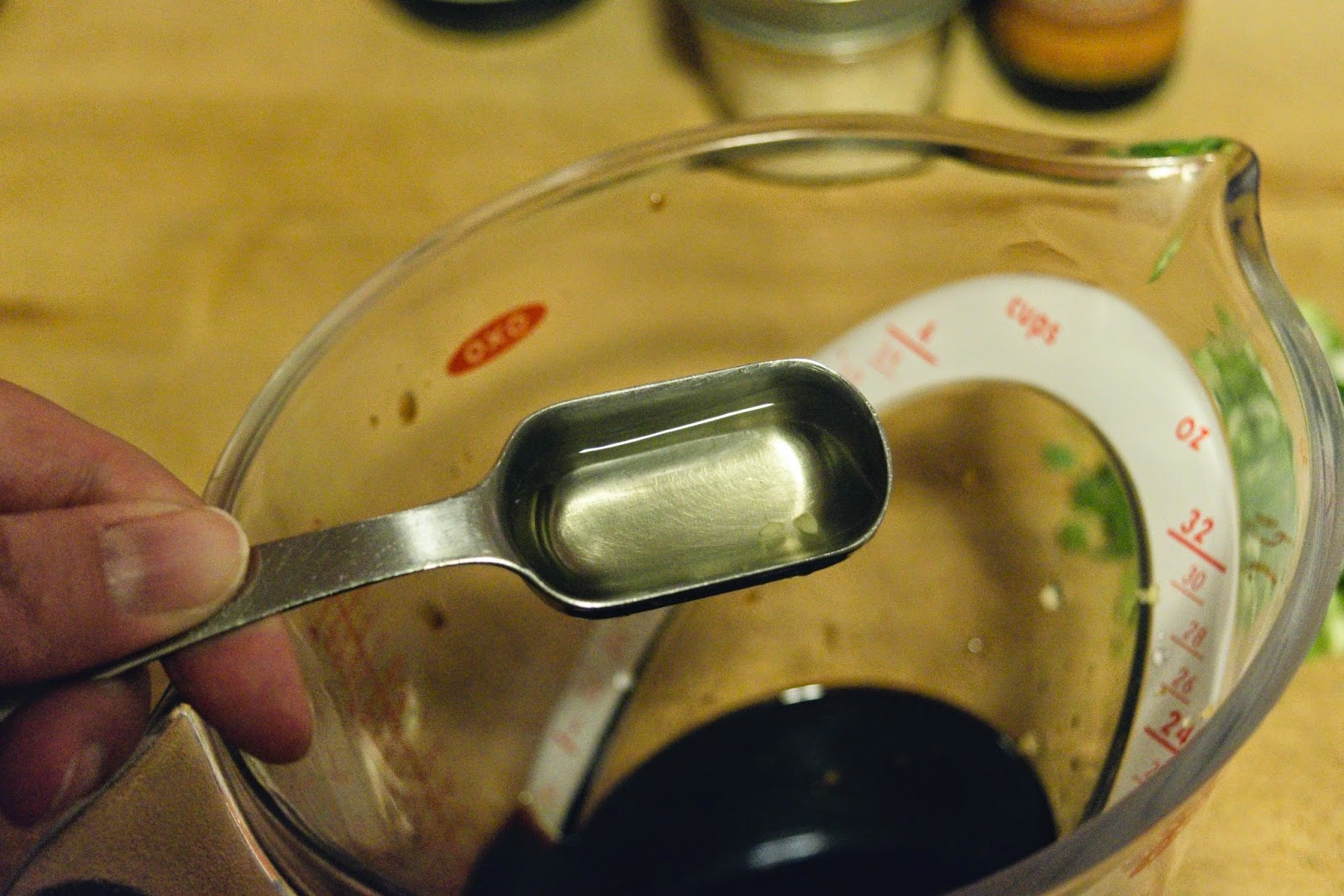White rice vinegar being added to the sauce in the measuring cup.