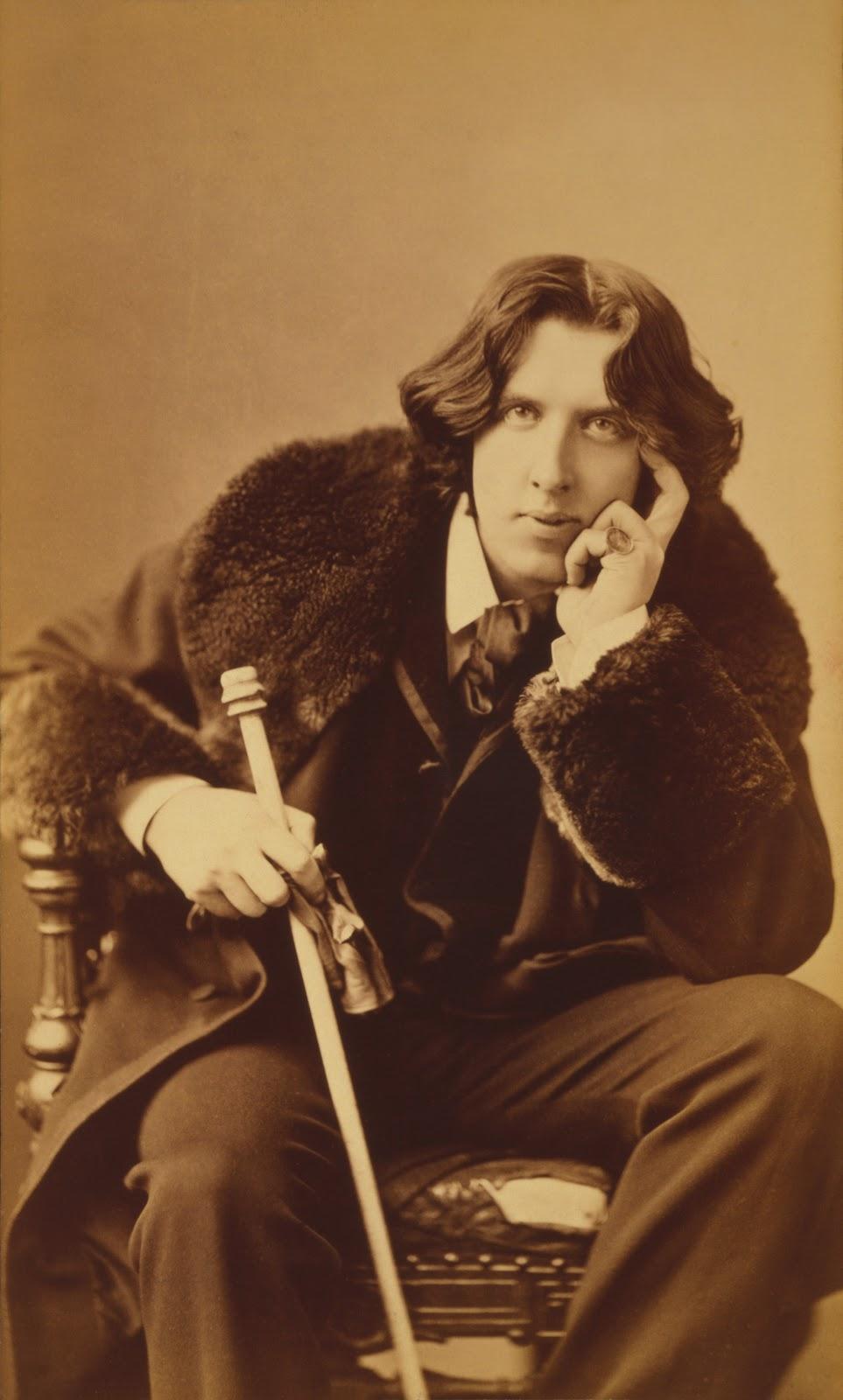 オスカー・ワイルドが椅子に座って正面を向いて右手で細長い杖を持って左手で頬杖を付いている
